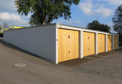 Garages alignés avec aménagement d'espace vert léger